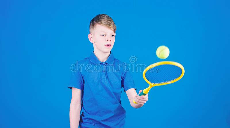 Athlete kid tennis racket on blue background. Tennis sport and entertainment. Boy child play tennis. Practicing tennis. Skills. Guy with racket enjoy game royalty free stock photography