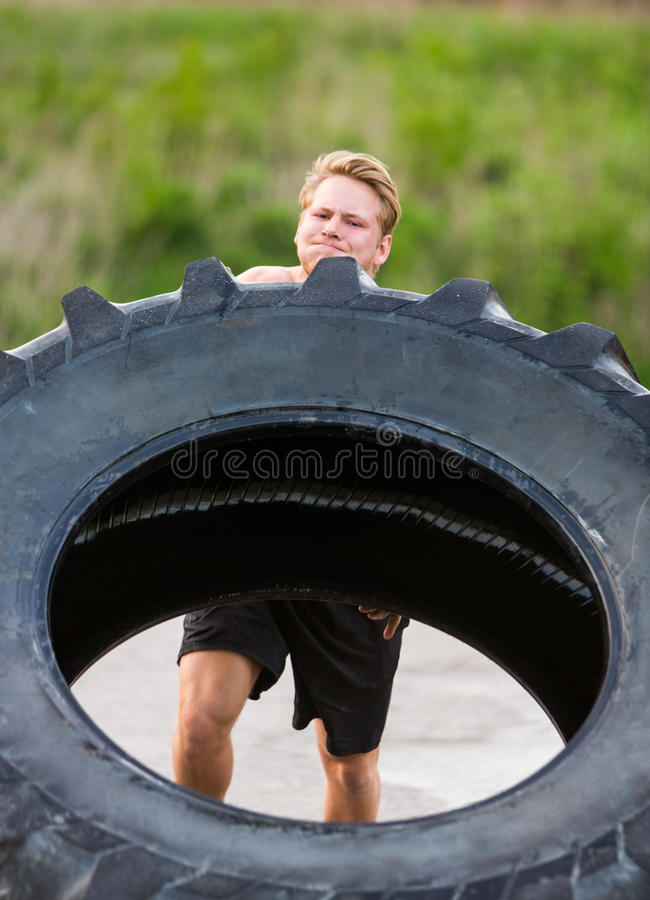Athlete Lifting Large Tractor Tire royalty free stock photo