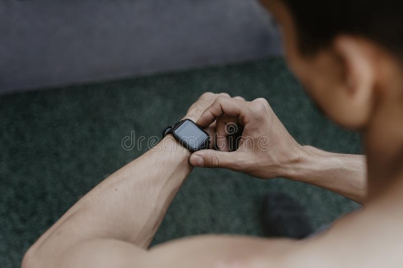 Athlete looking at his smartwatch fitness app after workout. Fitness gadgets concept. Space for text. Copy space royalty free stock photos