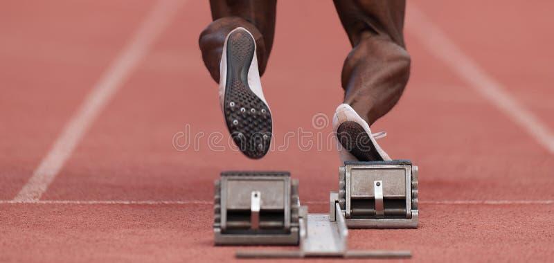 Athlete male feet on starting block stock photography