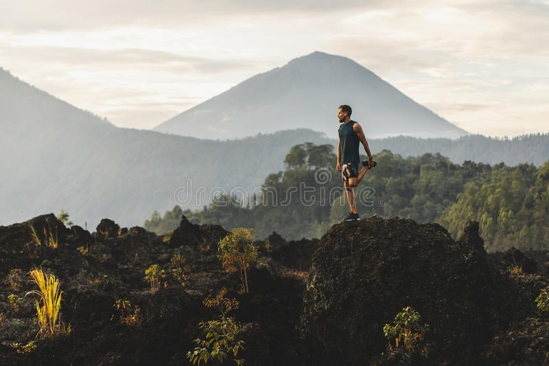 Athlete man doing stretching for workout outdoors. Man doing stretching and preparing for workout and running outdoors. Amazing mountain view on background stock image