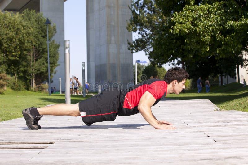 Athlete man making pushups stock photography