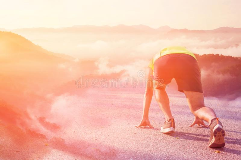 Athlete man in running start pose to mountain. Bright sunrise..Startup barrier stock image
