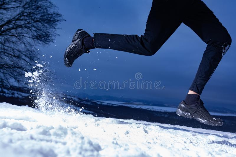 Athlete man is running during winter training outside in cold snow weather stock photo