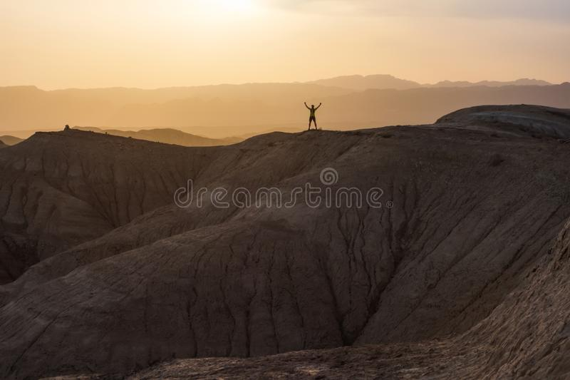 Athlete man stands on top of a hill. The joy of victory. Sunset in the mountains royalty free stock photo