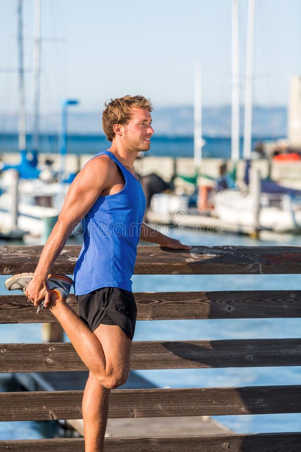 Athlete man stretching legs before running in San Francisco bay harbour - city lifestyle. Fitness runner doing warm-up before royalty free stock images