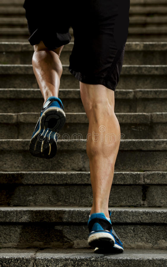Athlete man with strong leg muscles training and running urban city staircase in sport fitness and healthy lifestyle concept. Young athletic legs of runner sport stock image