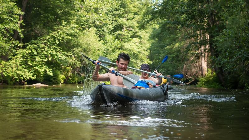 Athlete men in kayak with oars on wild river. Kayaking and sport recreation stock photography
