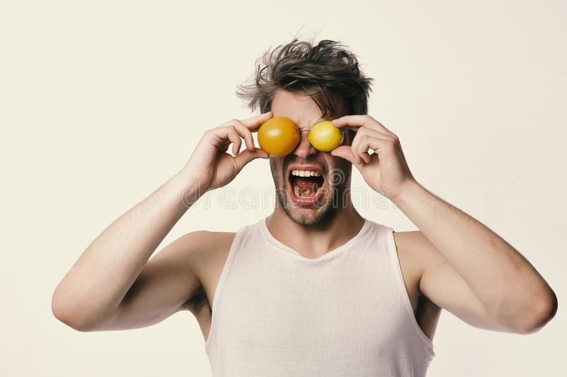 Athlete with messy hair holds fresh fruit. Man with fruit royalty free stock images