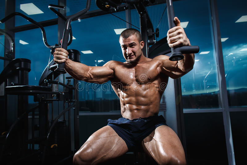 Athlete muscular bodybuilder training chest on simulator in the gym royalty free stock images