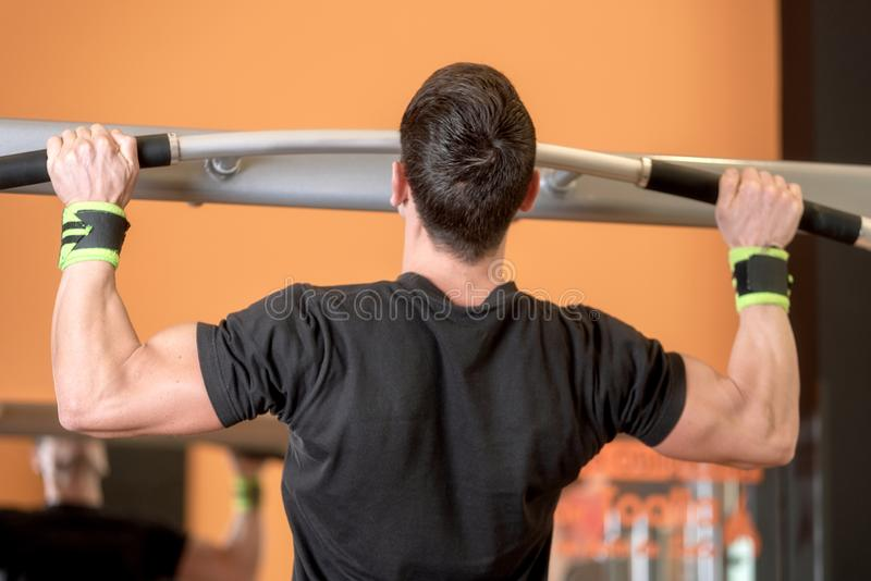 Athlete muscular fitness male model pulling up on horizontal bar in a gym. stock photography