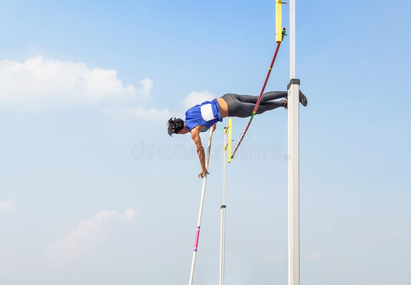 Athlete pole vault pole jumping competition over bar in to the sky royalty free stock photo
