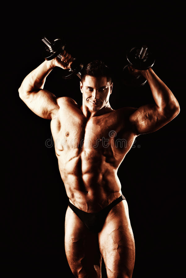 Athlete. Portrait of a handsome muscular bodybuilder posing with dumbbells over black background royalty free stock images