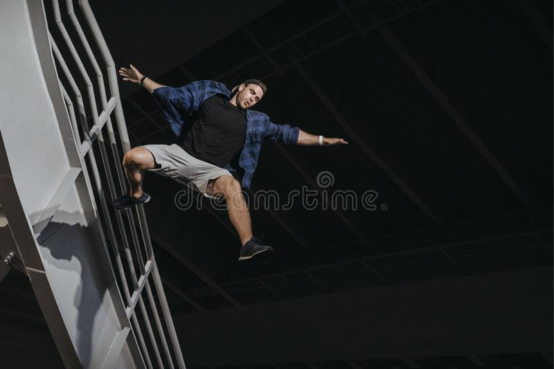 Athlete practicing freerunning doing big scary jump. Parkour like lifestyle stock photography