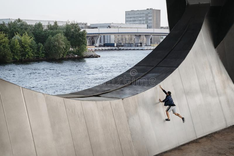 Athlete practicing frerunning, doing big wallrun exercise. Parkour in the city royalty free stock photos
