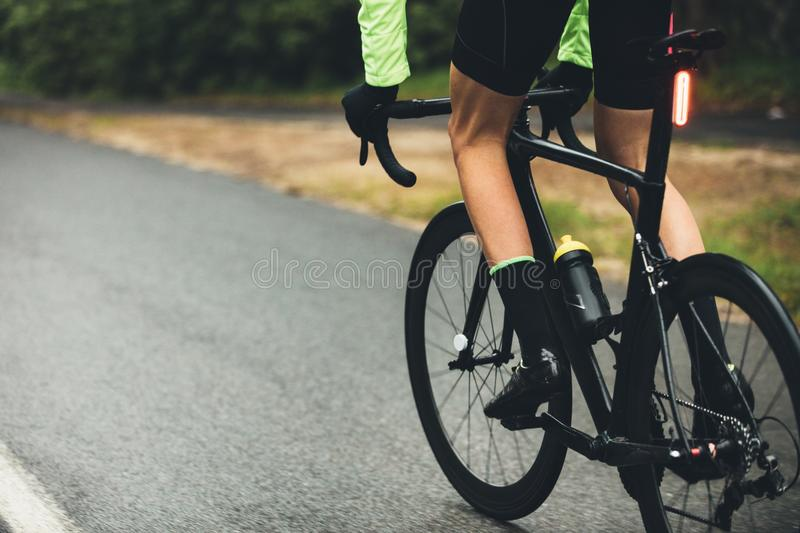 Athlete practising hard for cycle race. On the country road. Racer riding a bicycle on the road in countryside royalty free stock photos