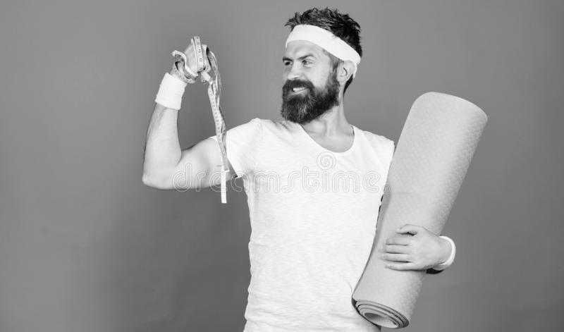 Athlete professional coach motivated for training. Athlete wear bandages for sweat. Man bearded athlete hold fitness mat. And tape measure. Athlete guide stay royalty free stock photography