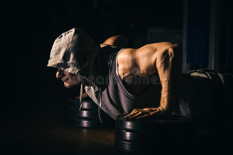 The athlete pushes, squeezes from the floor. Black background. stock image