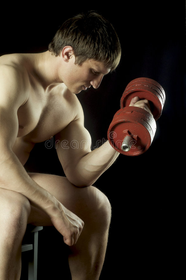 Athlete raises dumbbell. The young man of an athletic constitution plays sports royalty free stock images
