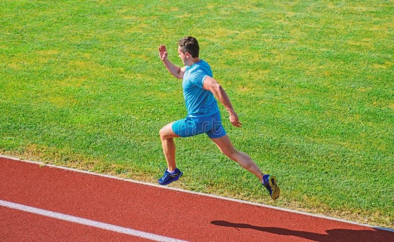Athlete run track grass background. Sprinter training at stadium track. Runner captured in midair. Short distance. Running challenge. Boost speed. Run into royalty free stock photography