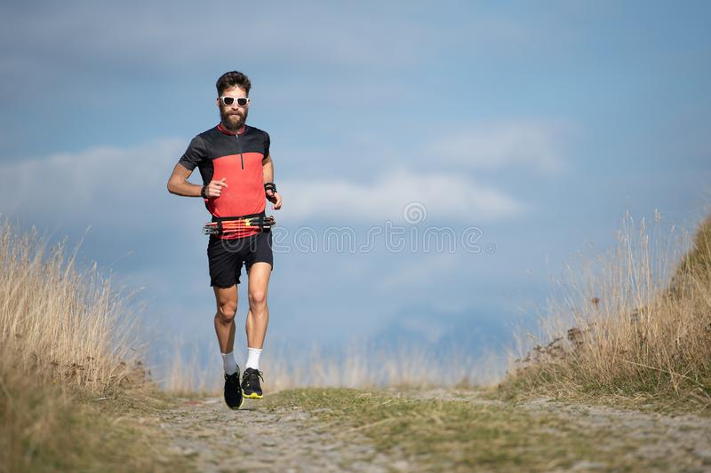 An athlete runner with a beard trains on a mountain road stock images