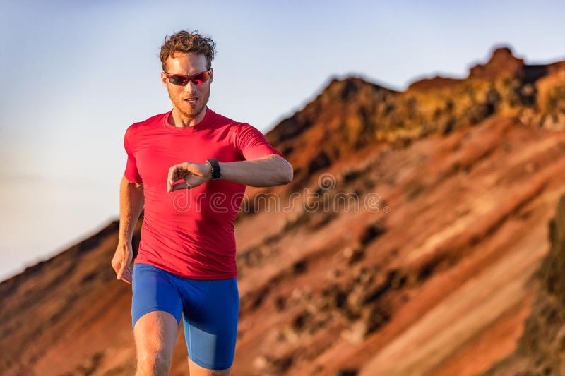 Athlete runner checking cardio on sports smartwatch jogging on outdoor run track. Running man wearing sunglasses and tech wearable. Device looking at watch royalty free stock photos