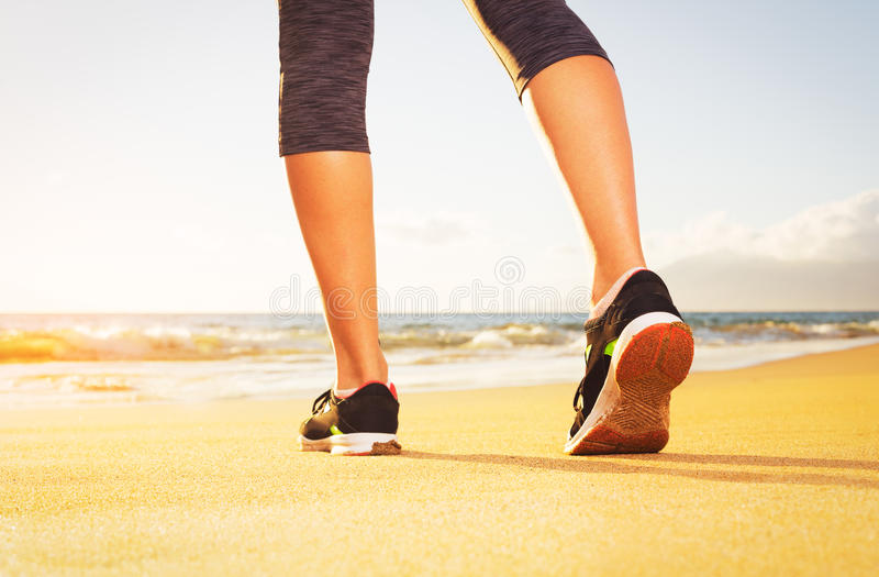 Athlete runner feet on the beach. Athlete runner feet running on the beach. Closeup on shoe and legs. Woman sunset fitness workout. Wellness healthy lifestyle royalty free stock photo