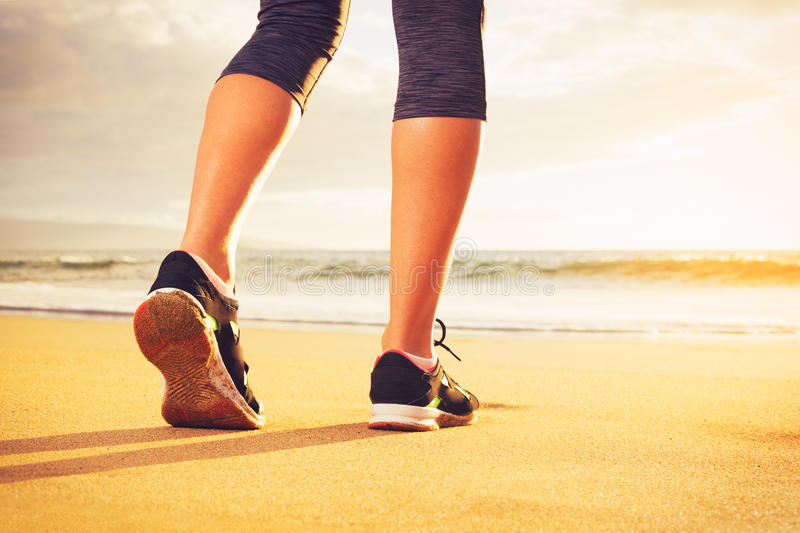 Athlete runner feet on the beach. Athlete runner feet running on the beach. Closeup on shoe and legs. Woman sunset fitness workout. Wellness healthy lifestyle stock image