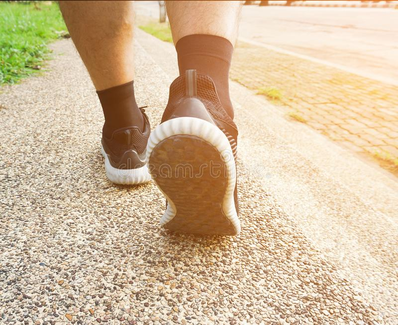 Athlete runner feet running in nature, close up on black shoe. men fitness jogging on the public, active lifestyle concept royalty free stock photo