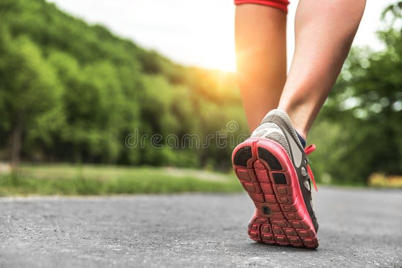 Athlete runner feet running on road. Runner feet running on road. Fitness and wellness concept stock photos