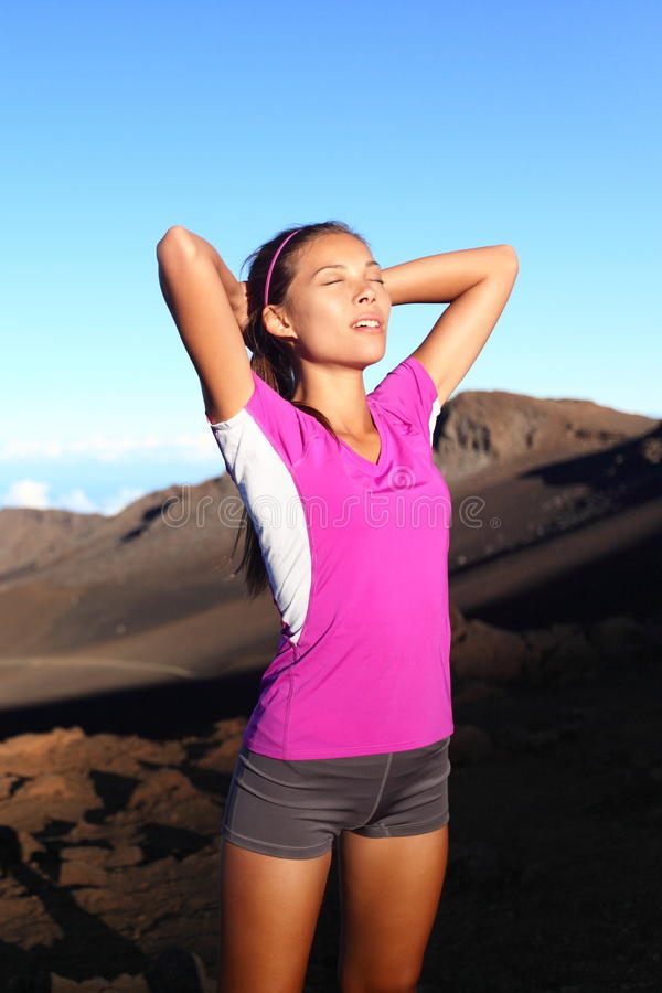 Athlete runner woman relaxing after running. Fitness girl resting after training outside in beautiful nature landscape. Fit sport fitness model outdoors at royalty free stock images