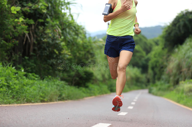 Athlete running on forest trail. woman fitness jogging workout wellness concept. Runner athlete running on forest trail. woman fitness jogging workout wellness royalty free stock image