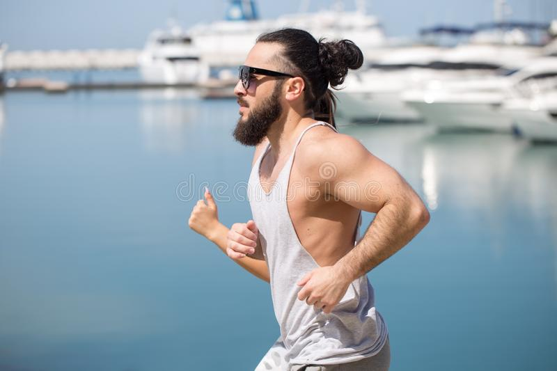 Athlete running man - male runner by the sea pier with yachts stock image