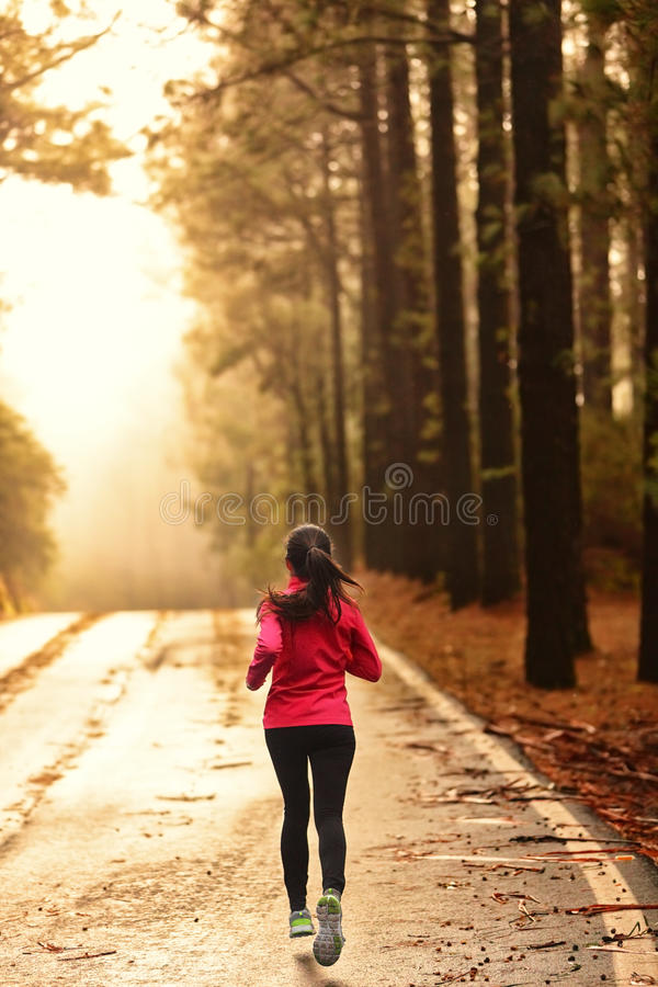 Athlete running on road in morning sunrise stock photo