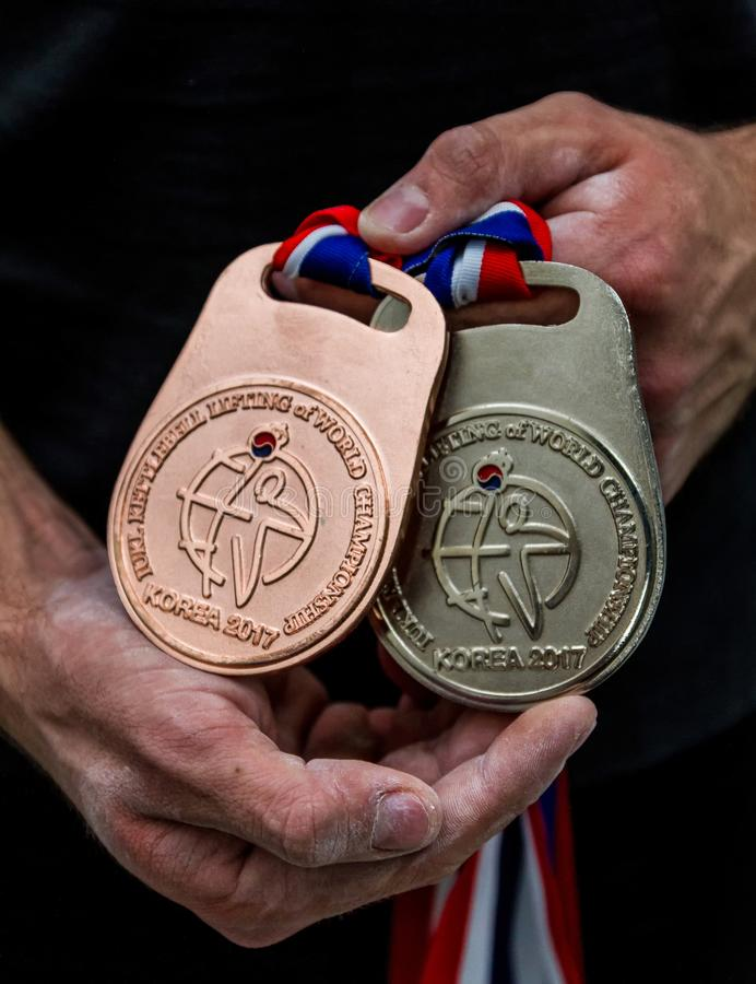 Athlete shows a bronze and a silver medals. Bronze and silver medals from the World Championship of kettlebell lifting in the hands of the athlete stock images