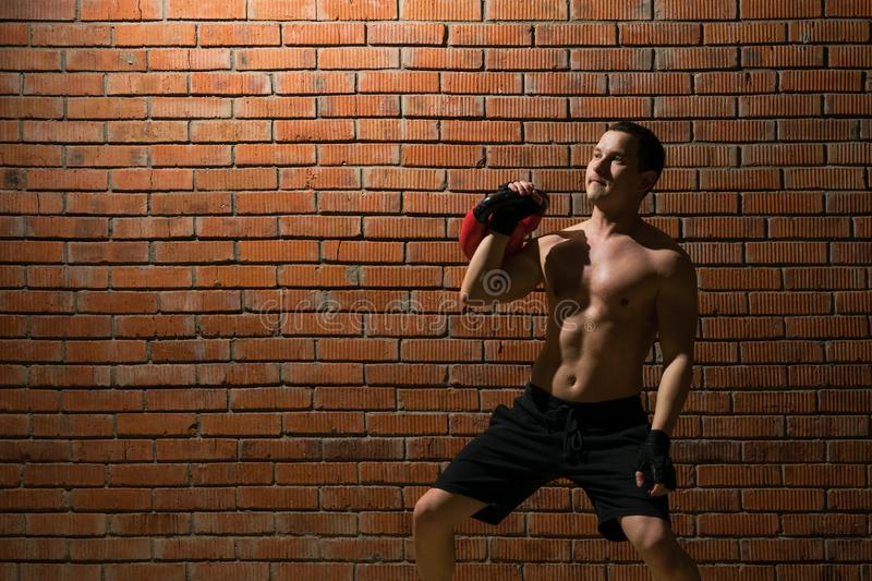 An athlete shows how to do an exercise with the weight to form a muscle in the fitness room on a red wall background royalty free stock photography