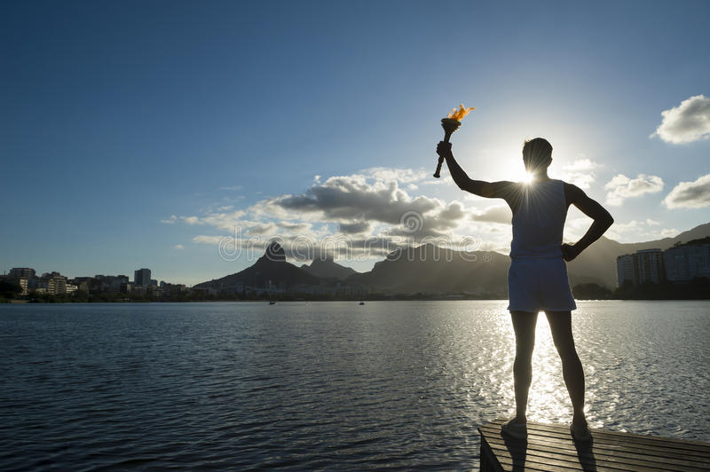 Athlete Silhouette Holding Sport Torch Rio de Janeiro. Silhouette of an athlete standing with sport torch against the the setting sun of the Rio de Janeiro royalty free stock images