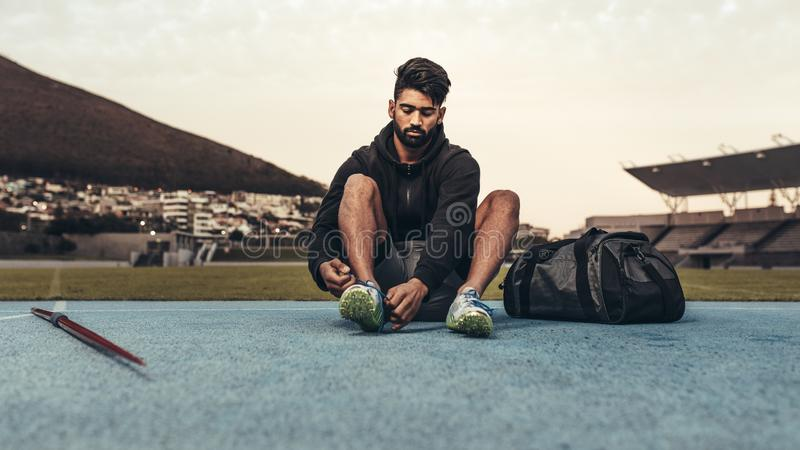 Athlete sitting on running track wearing his shoes. Athlete getting ready for training wearing shoes sitting in a track and field stadium. Man tying shoe lace stock image