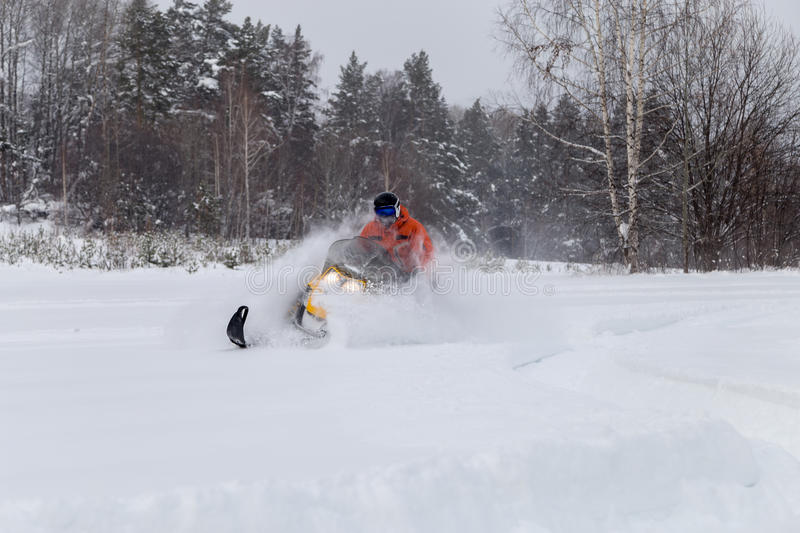 Athlete on a snowmobile. The sportsman on a snowmobile moving through deep snowdrifts in the winter forest in the mountains of the Southern Urals stock image