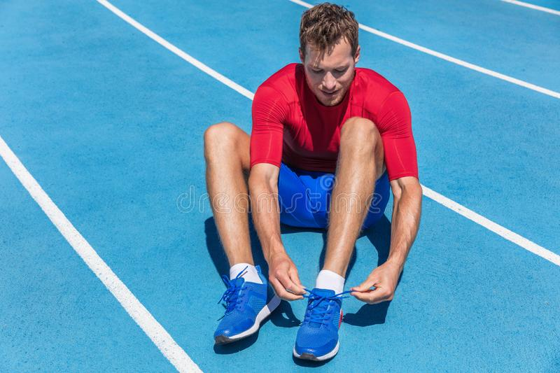 Athlete sprinter getting ready to run tying up shoe laces on stadium running tracks. Man runner preparing for cardio training. Outdoors. Fitness and sports stock photos