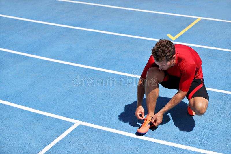 Athlete sprinter getting ready to run tying up shoe laces on stadium running tracks. Man runner preparing for race marathon. Training outdoors. Fitness and stock photography