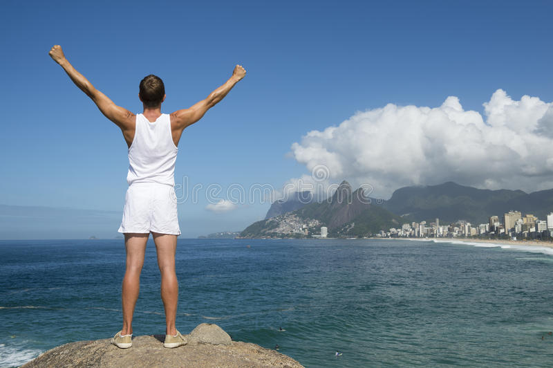 Athlete Standing Arms Raised Rio de Janeiro. Athlete in white sport uniform standing with champion arms raised in front of Rio de Janeiro Brazil skyline at royalty free stock photography
