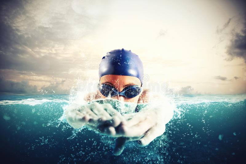 Athlete swims in a blue deep water stock photo