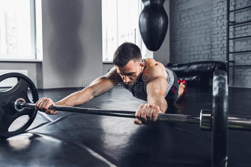 The athlete trains hard in the gym. Fitness and healthy life concept. Believe in yourself. The athlete trains in the gym, doing strength and special exercises royalty free stock photo