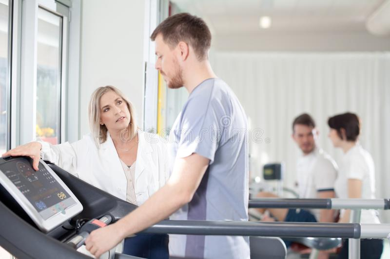 Athlete on a treadmill with physiotherapist doctor. Athlete on the treadmill he performs the instructions of physical therapist who assists him. in the stock photos
