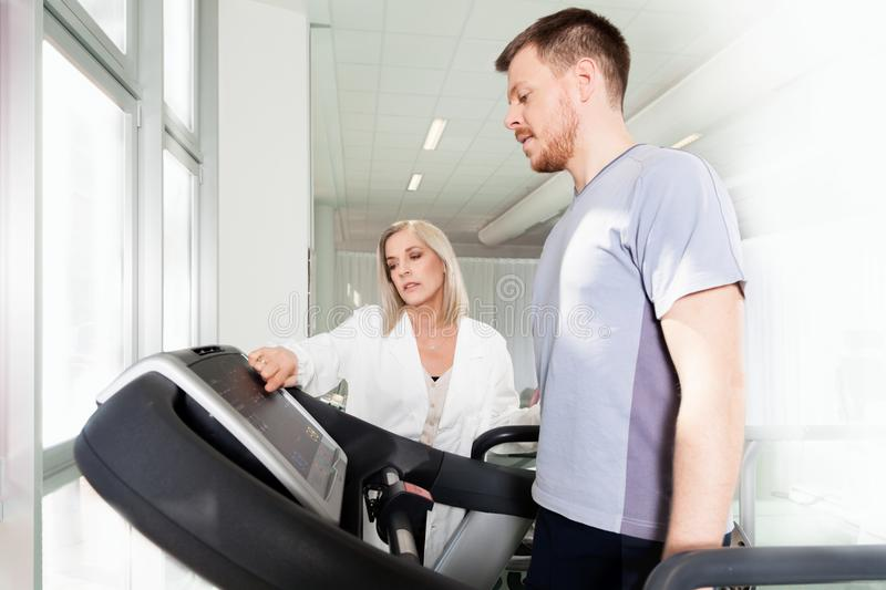 Athlete on a treadmill with physiotherapist doctor. Athlete on the treadmill he performs the instructions of physical therapist who assists him. in the royalty free stock photos