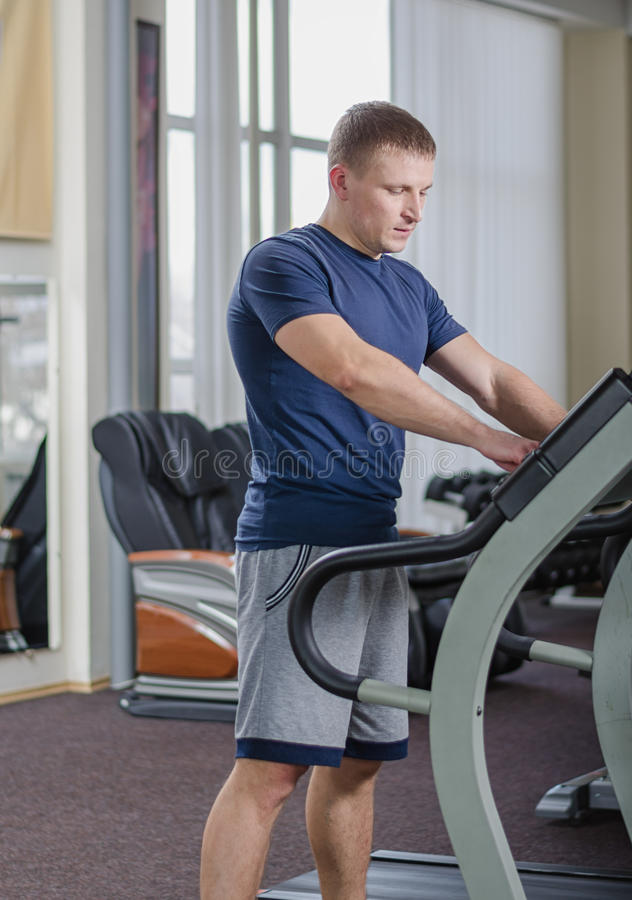 Athlete on the treadmill. Young athlete in the gym warming up (running) on a treadmill royalty free stock photos