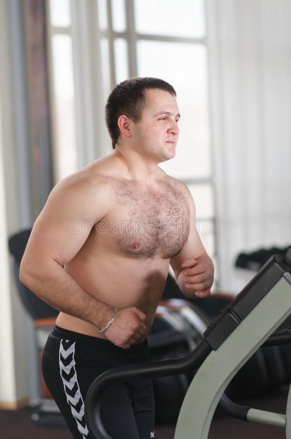 Athlete on the treadmill. Young athlete in the gym warming up (running) on a treadmill stock image