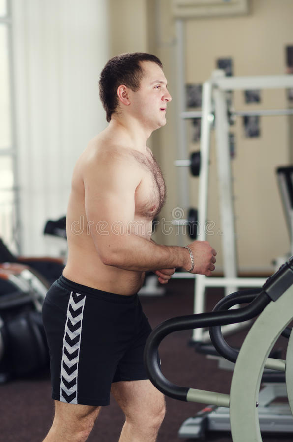 Athlete on the treadmill. Young athlete in the gym warming up (running) on a treadmill stock photos