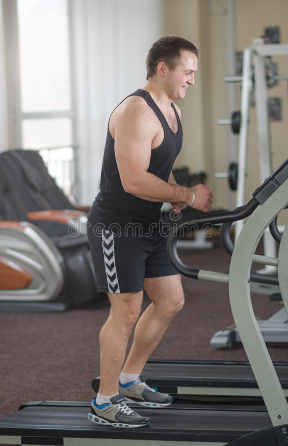 Athlete on the treadmill. Young athlete running at the gym on the treadmill stock photography